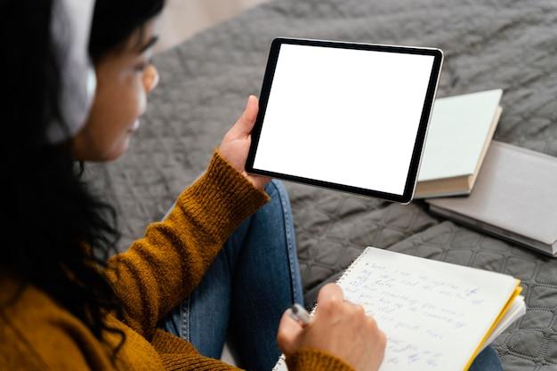 Alto ángulo de adolescente con tableta para escuela en línea