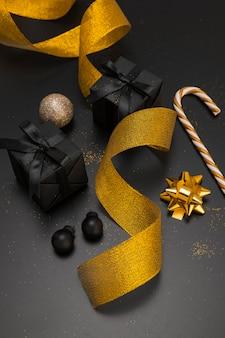 Alto ángulo de adornos navideños con cinta dorada y regalos.