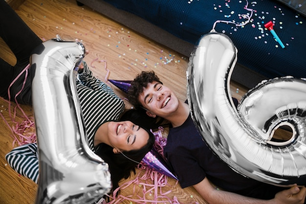Alto ángulo amigos felices riendo y sosteniendo globos