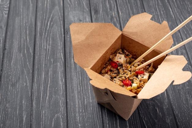 Alto ángulo de arroz y verduras para llevar y palillos con espacio de copia