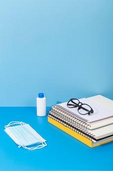 Alto ángulo de artículos de regreso a la escuela con desinfectante para manos y mascarilla