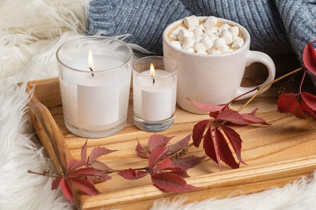 Alto ángulo de bandeja con velas y taza de chocolate caliente con malvaviscos