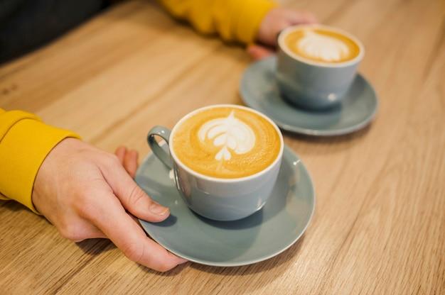 Alto ángulo de barista con dos tazas de café.