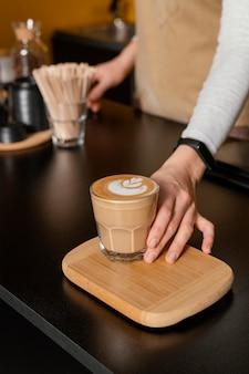 Alto ángulo de barista femenina sosteniendo un vaso de café decorado