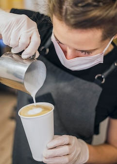 Alto ángulo de barista hembra vertiendo leche en la taza de café