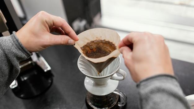 Alto ángulo de barista masculino despegando el filtro de café