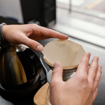 Alto ángulo de barista masculino preparando filtro de café