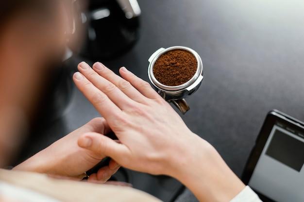 Alto ángulo de barista masculino preparando la taza de café