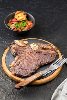 Alto ángulo de bistec con cubiertos y ensalada