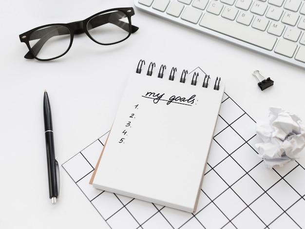 Alto ángulo de bloc de notas con objetivos y gafas