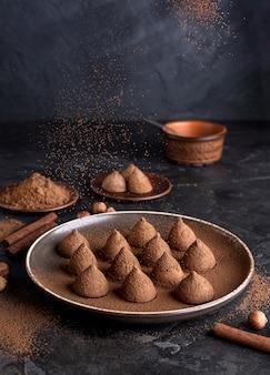 Alto ángulo de bombones de chocolate con cacao en polvo y palitos de canela