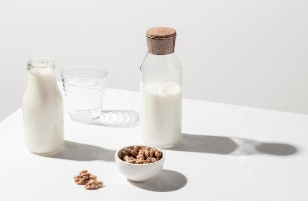 Alto ángulo de botella de leche con vaso vacío y tazón de nueces