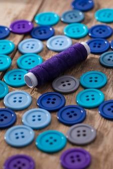 Alto ángulo de botones azules con carrete de hilo