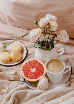 Alto ángulo de café de la mañana con pomelo y macarons