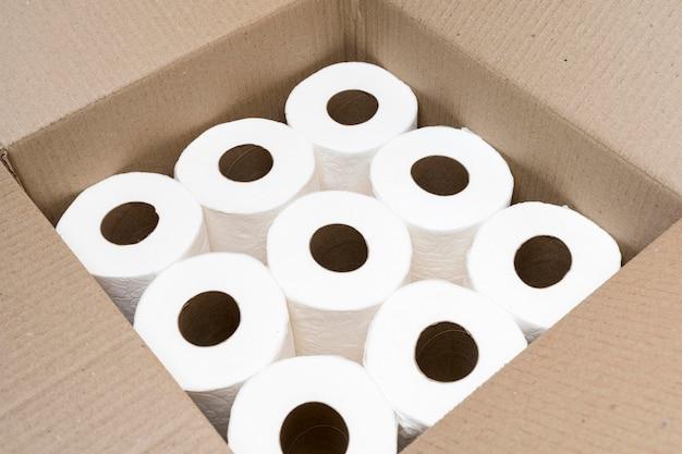 Alto ángulo de caja de cartón con rollos de papel higiénico.