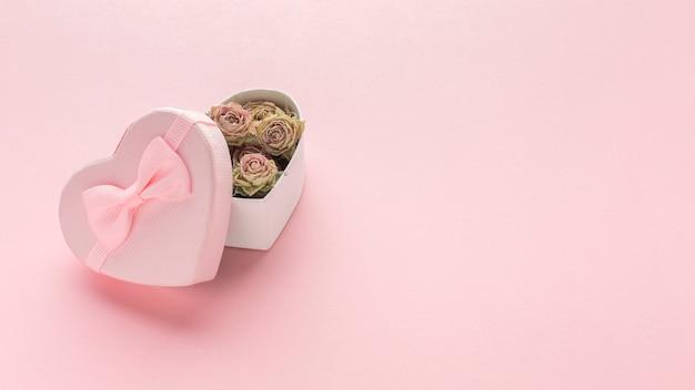 Alto ángulo de caja de regalo rosa con rosas