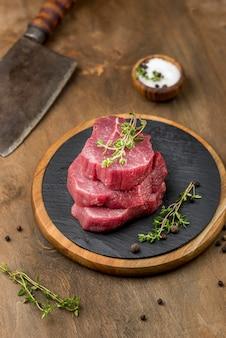 Alto ángulo de carne apilada con hierbas y sal
