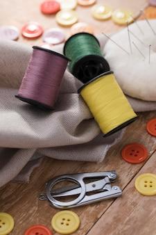 Alto ángulo de carretes de hilo con textil y botones.