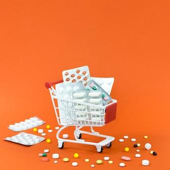 Alto ángulo del carrito de compras con láminas de pastillas y espacio de copia