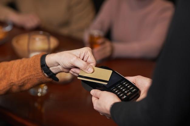 Alto ángulo de cerca del hombre irreconocible pagando con tarjeta de crédito, se centran en las manos que sostienen la tarjeta sobre la terminal, copie el espacio
