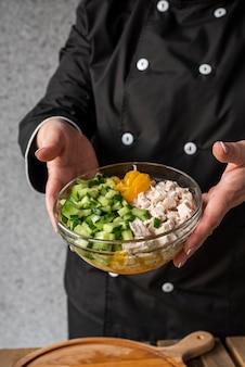 Alto ángulo de chef mujer sosteniendo tazón con ingredientes