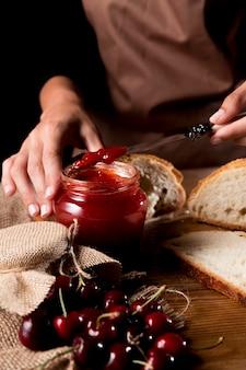 Alto ángulo de chef con tarro de mermelada de cerezas