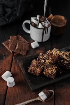 Alto ángulo de chocolate caliente y brownies con nueces