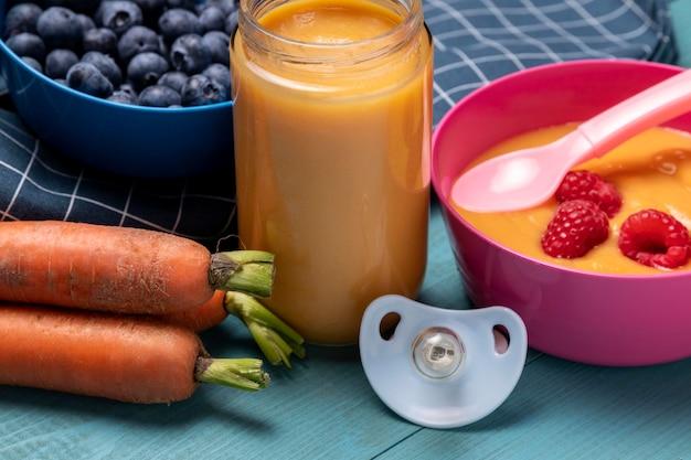Alto ángulo de comida para bebés con zanahorias y arándanos