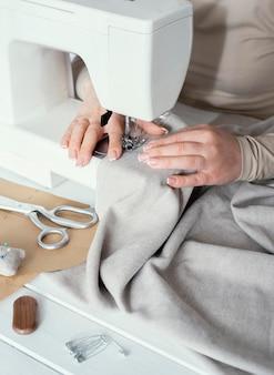 Alto ángulo de costurera con máquina de coser