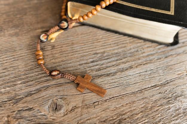 Alto ángulo de cruz rosario con libro sagrado