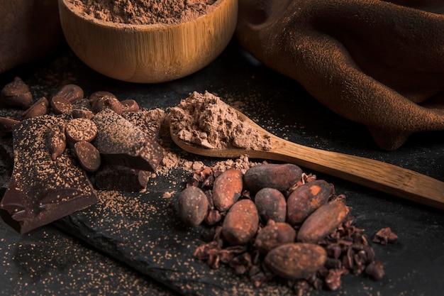 Alto ángulo delicioso arreglo de chocolate sobre tela oscura