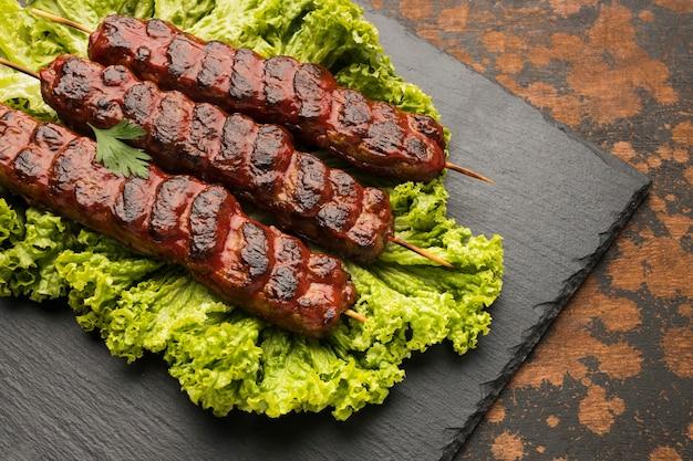 Alto ángulo de delicioso kebab en pizarra con ensalada