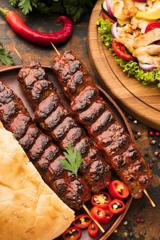 Alto ángulo de delicioso kebab con verduras y hierbas.