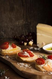 Alto ángulo delicioso queso con composición de tomates en la mesa
