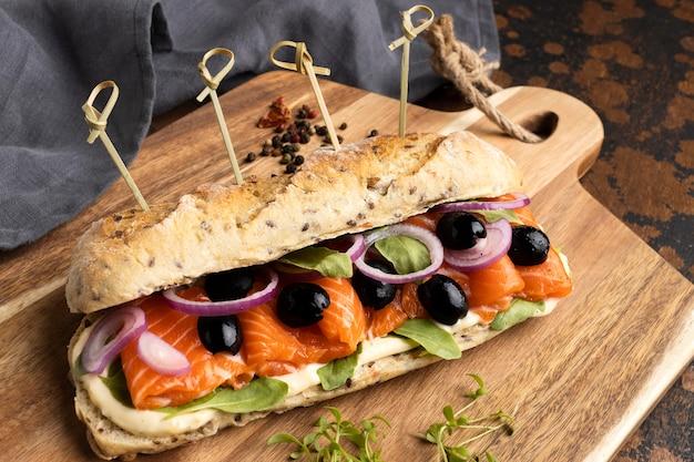 Alto ángulo de delicioso sándwich de salmón con aceitunas y cebollas