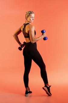 Alto ángulo de entrenamiento femenino joven con pesas