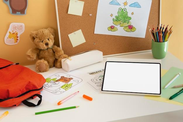 Alto ángulo de escritorio para niños con mochila y tableta