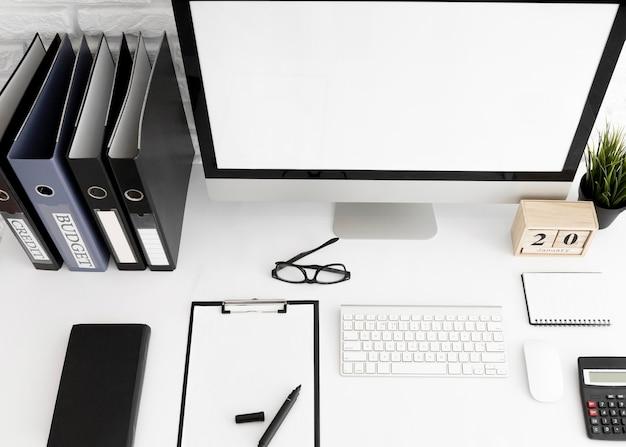 Alto ángulo de escritorio de oficina con pantalla de computadora y portapapeles