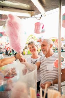 Alto ángulo feliz pareja comprando algodón de azúcar