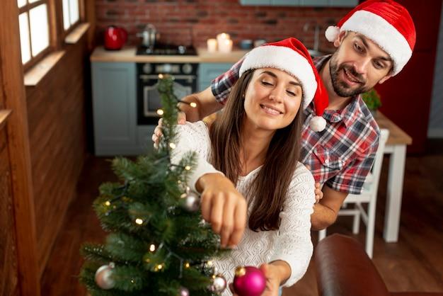 Alto ángulo feliz pareja decorando el árbol de navidad