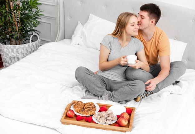 Alto ángulo feliz pareja con desayuno en la cama