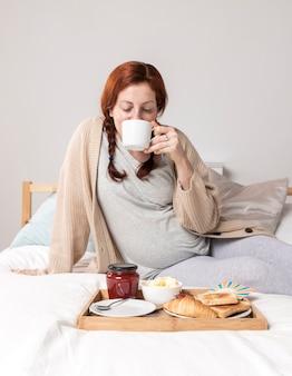 Alto ángulo femenino disfrutando de brunch en la cama