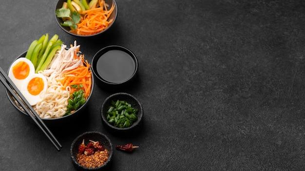 Alto ángulo de fideos asiáticos tradicionales con verduras y espacio de copia