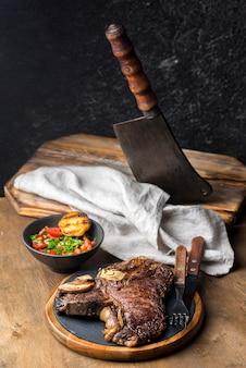Alto ángulo de filete con ensalada y cuchilla