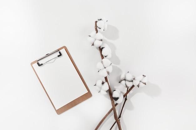 Alto ángulo de flores de algodón y un papel en blanco sobre una superficie blanca