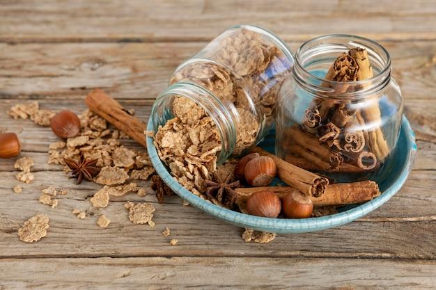 Alto ángulo de frascos con cereales para el desayuno y palitos de canela
