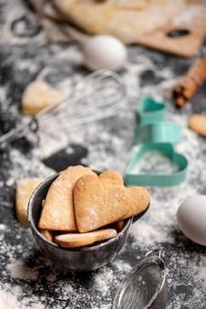 Alto ángulo de galletas del día de san valentín con batidor y huevos