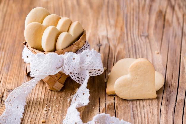 Alto ángulo de galletas en forma de corazón en la cesta con arco