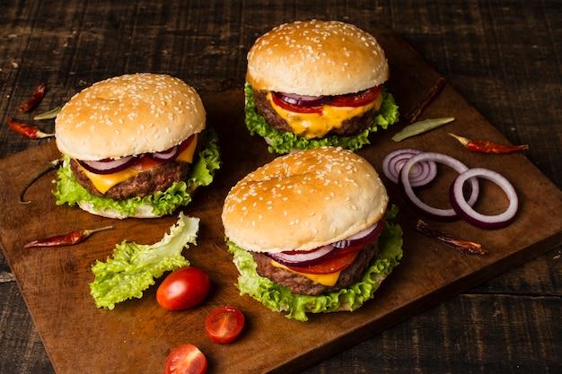 Alto ángulo de hamburguesas en bandeja de madera.