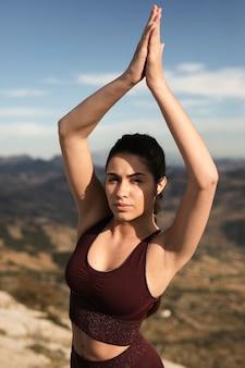 Alto ángulo hembra joven en la luz del sol haciendo yoga